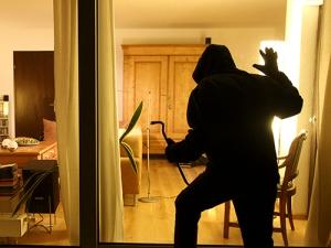 Symbolbild Einbruch, Einbrecher will in ein Haus eindringen, schleicht sich auf der Terrasse an, beobachtet durch ein Fenster ob die Bewohner zuhause sind.